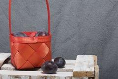 Ameixas perfumadas maduras em uma cesta de vime Localizado em uma caixa de madeira, batida fora das placas fotografia de stock