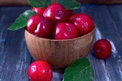 Ameixas vermelhas na tabela de madeira Imagens de Stock