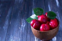 Ameixas vermelhas na tabela de madeira Foto de Stock