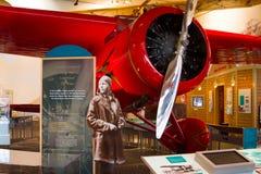 Amelia Earhart y mujer roja de Lockheed 5B Vega primera para intentar t Imagenes de archivo
