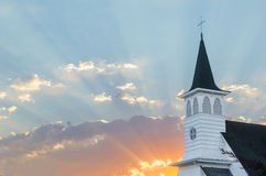 Amen. Golden rays of sun burst through the clouds at sunrise with an old Christian church steeple in the far right stock photography