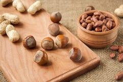Amendoim, avelã em umas bacias de madeira em de madeira e serapilheira, fundo do saco Imagens de Stock