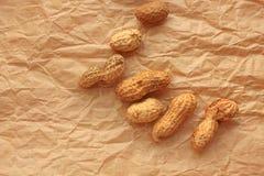 Amendoim em um escudo no papel de embalagem, fundo do alimento dos amendoins fotografia de stock royalty free