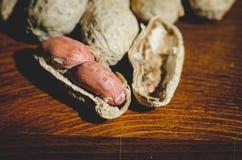 Amendoins frescos no shel e descascados sem shell no fim de madeira do fundo da tabela acima foto de stock