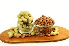 Amendoins inteiros e descascados no fundo branco Imagens de Stock