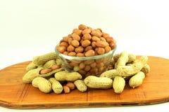 Amendoins inteiros e descascados no fundo branco Imagem de Stock Royalty Free