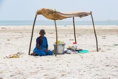 Amendoins não identificados dos frutos da venda da mulher a um cliente, sob uma barraca na praia de Danushkodi fotos de stock