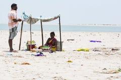 Amendoins não identificados dos frutos da venda da mulher a um cliente, sob uma barraca na praia de Danushkodi imagem de stock royalty free