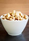 Amendoins na placa branca Imagens de Stock