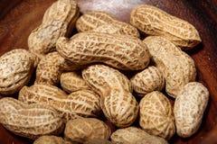 Amendoins no macro de madeira do close up do prato Imagem de Stock Royalty Free