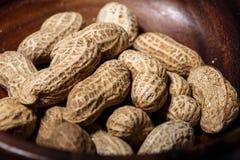 Amendoins no macro de madeira do close up do prato Foto de Stock