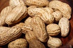 Amendoins no macro de madeira do close up do prato Fotos de Stock Royalty Free