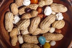 Amendoins no prato de madeira com macro do close up dos doces Imagem de Stock Royalty Free