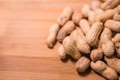 Amendoins nos escudos em uma superfície de madeira natural foto de stock royalty free