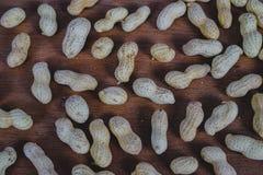 Amendoins nos escudos na tabela de madeira imagens de stock