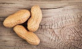 Amendoins nos shell no fundo de madeira Foto de Stock