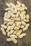 Amendoins nos shell no fundo de madeira Fotos de Stock