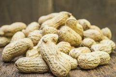 Amendoins nos shell no fundo de madeira Fotografia de Stock Royalty Free