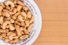 Amendoins salgados e roasted na bacia branca na tabela de madeira Fotos de Stock
