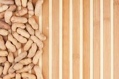Amendoins Unpeeled que encontram-se em uma esteira de bambu Imagens de Stock Royalty Free