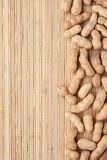 Amendoins Unpeeled que encontram-se em uma lata de bambu da esteira Imagem de Stock