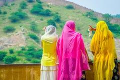 Amer, Inde - 19 septembre 2017 : Femmes non identifiées posant dans un mur lapidé, portant des vêtements jaunes et roses, et Photos stock