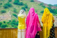 Amer, India - September 19, 2017: Unidentified women posing in a stoned wall, wearing a yellow and pink clothes, and