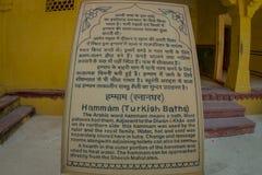 Amer Indien - September 19, 2017: Informativt tecken som är skriftligt i indiskt och engelskt språk över en asfull struktur i Royaltyfri Bild