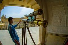 Amer, la India - 19 de septiembre de 2017: Hombre no identificado que manipula un telescopio de oro dentro del palacio en Amer, a Foto de archivo