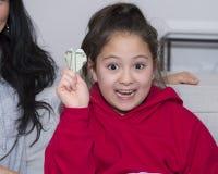 Amerasian女孩热心对她的圣诞节礼物,一张二十美金被做成心脏通过oragami 免版税图库摄影