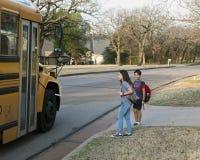 Amerasian barn som är klara att stiga ombord skolbussen royaltyfri foto