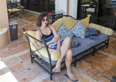 Amerasian beauty relaxing on an outdoor sofa royalty free stock images