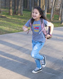 Amerasian girl running for the school bus Royalty Free Stock Photo
