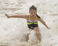 Amerasian girl splashing in the ocean waves Stock Image