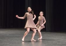 Amerasian sisters perform jazz duet. Pictured are a thirteen year old and nine year old Amerasian sisters performing a jazz duet in a dance competition.  They Stock Images