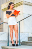 Amercan female college student reading book, studying on campus. College Student. Dressing in black, short sleeve top, white short wrap skirt, high heels, a Stock Image