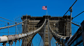 America. The American flag blows atop the Brooklyn Bridge Stock Image