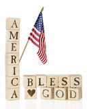 America, Bless God. Rustic alphabet blocks arranged to say America, Bless God, with an American flag flying above.  On a white background Stock Image