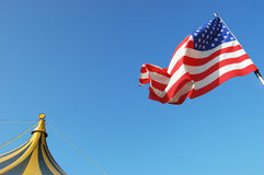 America and Circus. An american flag waving near the top of a circus tent Royalty Free Stock Photos