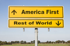 America and rest of world. Yellow traffic and direction sign with two arrows showing up and down and the words America first and Rest of world. Concept Royalty Free Stock Photography