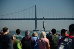 America's Cup 2013. Fans watching America's Cup team sail under the Bay Bridge Royalty Free Stock Photo