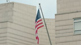 Slow Motion America`s flag stars and stripes on the building of the US Embassy in Berlin, Germany. The concept of. America`s flag stars and stripes on the stock video footage
