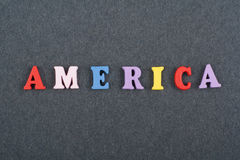 America word on black board background composed from colorful abc alphabet block wooden letters, copy space for ad text royalty free stock photo