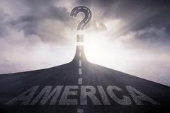 America word and question mark on road. Empty road leading to a question mark and symbolizing uncertainty with a word of America on the street Stock Images