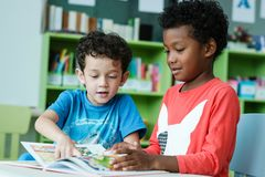 American and African boys are reading together with happiness in. Their kindergarten classroom, kid education and diversity concept Royalty Free Stock Photography
