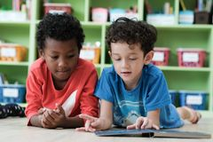 American and African boys are reading together with happiness in. Their kindergarten classroom, kid education concept Royalty Free Stock Photography