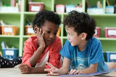 American and African boys are reading together with happiness in. Their kindergarten classroom, kid education and diversity concept Stock Image