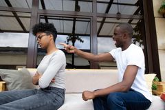 Angry black husband negative emotionally shouting at wife. American african married couple sitting on couch in summer terrace and quarrelling. Angry husband stock photography