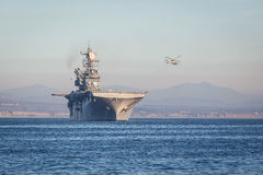 American aircraft carrier. A helicopter approaches an American aircraft carrier off the coast of california near camp pendleton stock image