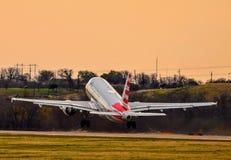 American Airlines Airbus A319, der während eines Sonnenuntergangs sich entfernt stockfotos